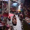 Tourists enjoying themselves in rowing boats at Damnoen Saduak floating market. Visit Damnoen Saduak on our private floating market tour from Bangkok.