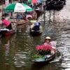 Vendors selling flowers and fruits at Damnoen Saduak floating market
