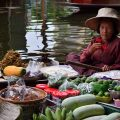 A boat with cooking supplies is passing by another one selling local snacks at Damnoen Saduak floating market