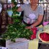 Vendor packing roses in old newspapers at Bangkok's biggest flower market