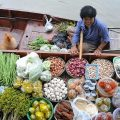 A shopper stops by to chat with the vendor at Tha Kha floating market